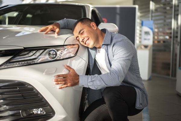 A man hugging his car happy for has got an insurance with DiskQuote.