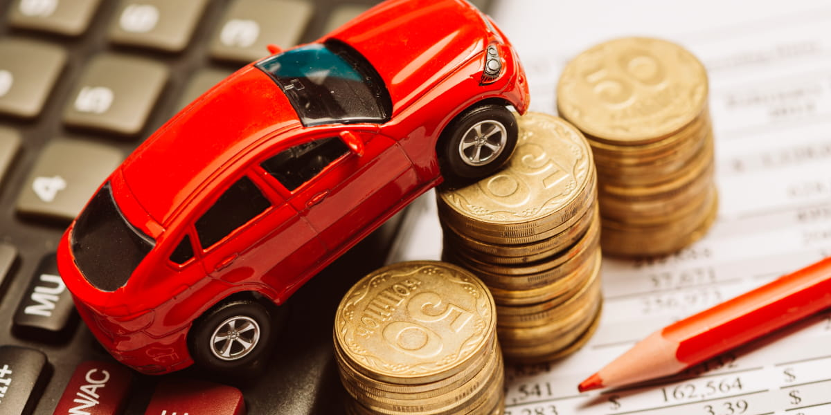 An overhead view of toy car over calculator and coin.