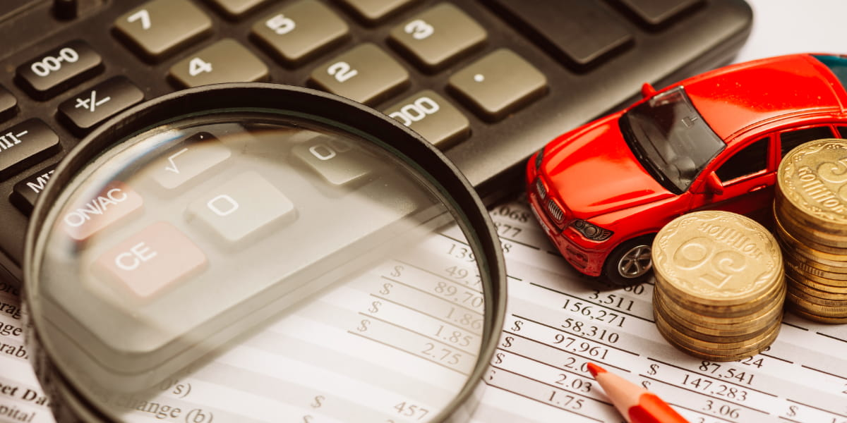 Magnifying glass over the calculator and financial report with car and coin.