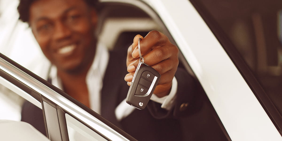 A black man holding the key to his new car.