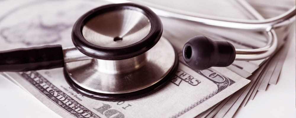 Closeup of cash and a stethoscope healthcare and expenses concept about Insurance Plan.