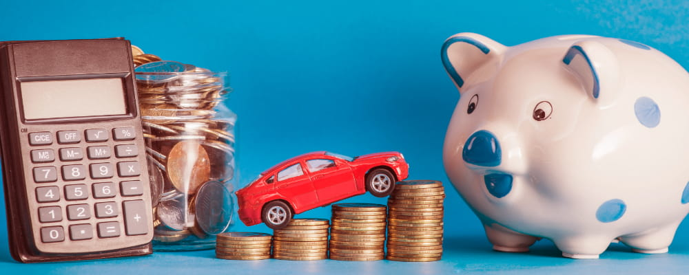 Car over the coin stack with calculator; glass jar; ceramics piggybank against blue background
