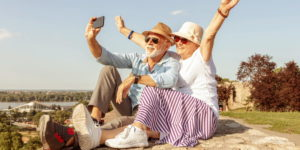 Couple raising her hands while taking a selfie.