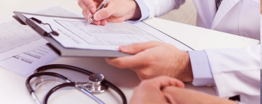 Close-up of a doctor filling the health insurance form with patient
