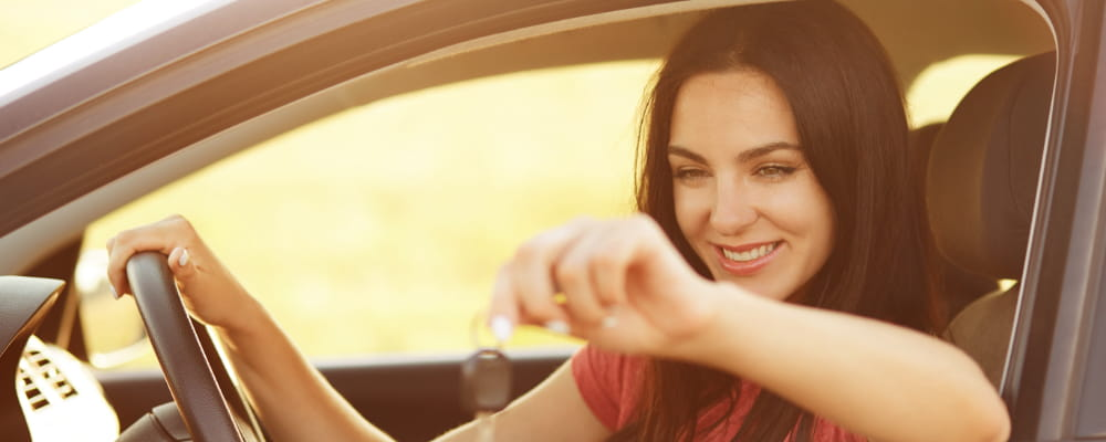 Glad female driver holds keys from car.