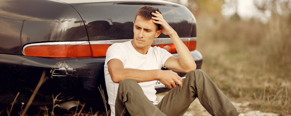 Man sitting near the broken car thinking about car insurance limits