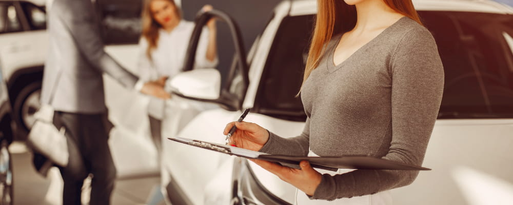 Two stylish woman in a car salon sing a insurance form.