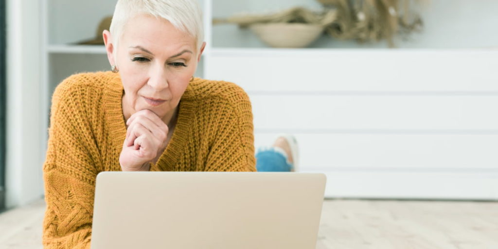 Elderly woman thinking and looking at laptop.