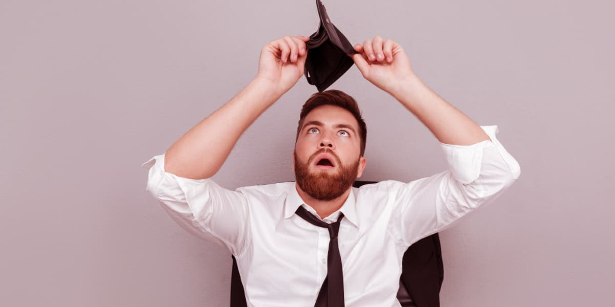 Frustrated surprised bearded man in white shirt showing empty wallet.