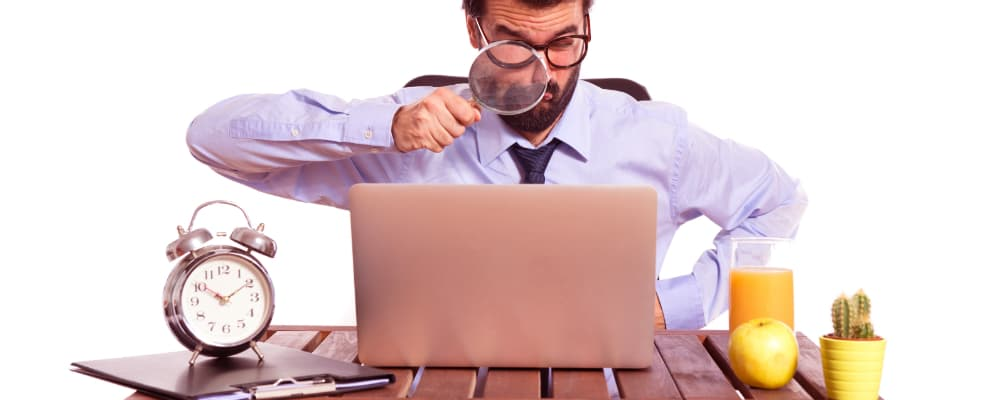 Businessman in his office with magnifying glass.