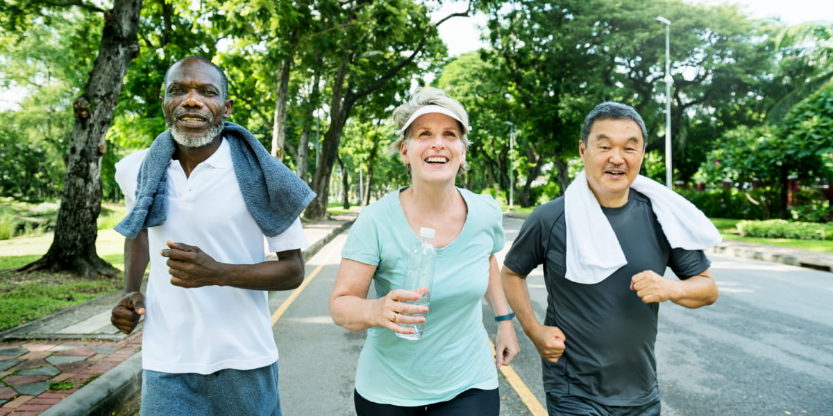Group of senior friends jogging together in a park.
