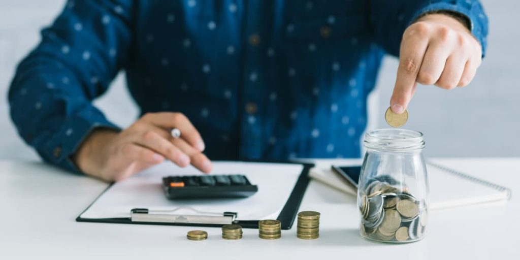 Businessman putting coins in jar using calculator at workplace.